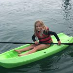 Young girl having a blast kayaking by her self like a big girl