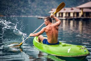 Strong young man in kayak burning calories