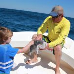 Young boy rubs a fish on the back of the boat