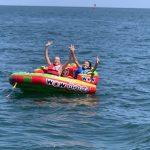 Having a blast behind the boat in their tubing fun