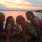 You family and friends enjoying themselves smiling during a sunset photo