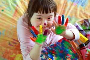 Cute little girl with painted hands doing fun activities for kids